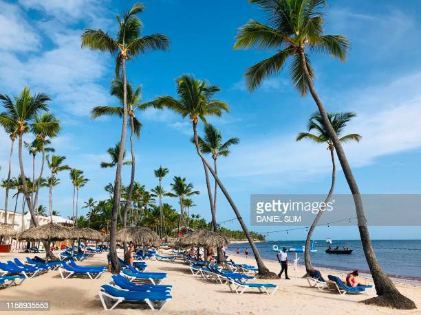 Tourists enjoy the beach near a private security guard in Punta Cana Dominican Republic on August 1 2019