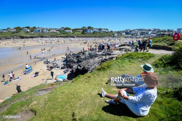 Tourists enjoy the beach on July 30 2020 in Polzeath United Kingdom Tourists are slowly returning to Cornwall after lockdown measures introduced to...