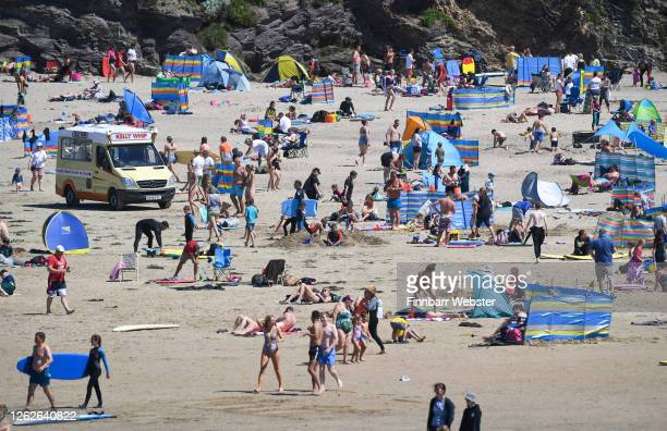 Tourists enjoy the beach on July 30, 2020 in Polzeath, United Kingdom. Tourists are slowly returning to Cornwall after lockdown measures introduced...