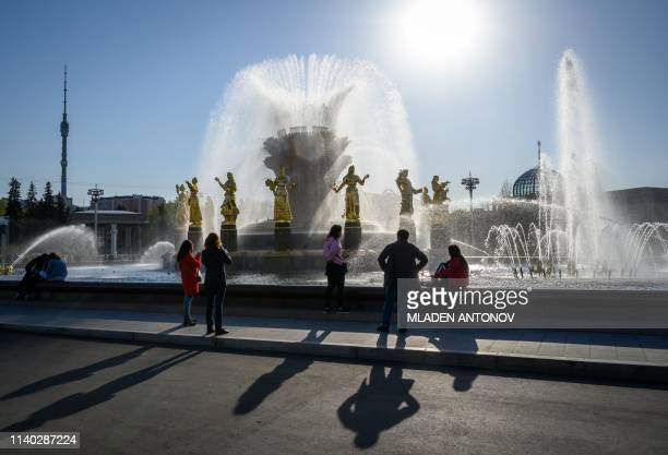 Tourists enjoy the Friendship of Nations fountain at VDNKh on the day of its reopening following restoration in Moscow on April 30 2019 The...