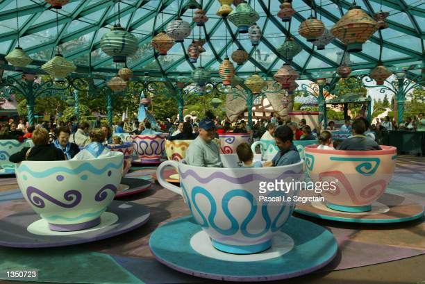 Tourists enjoy the Mad Hatter's Tea Cups in Fantasyland at Disneyland Paris August 22 2002 in Marne la Vallee France After a rocky start ten years...