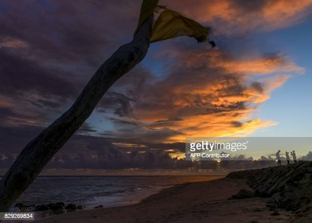 Tourists enjoy the sunset at Lhoknga beach in Aceh province on August 10 2017 / AFP PHOTO / CHAIDEER MAHYUDDIN