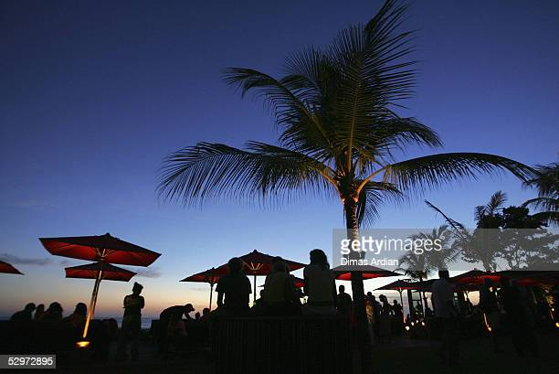Tourists enjoy the sunset in Ku de ta cafe on Seminyak beach on May 24 2005 in Bali Indonesia Australian travel agents have threatened to stop...