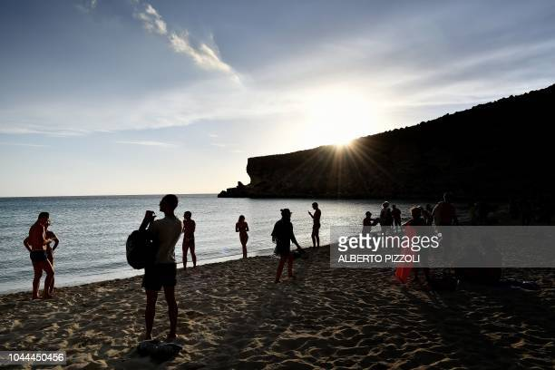 Tourists enjoy the sunset on the beach of the Isola dei Conigli in Lampedusa on September 25 2018 Five years after the worst shipwreck of its history...