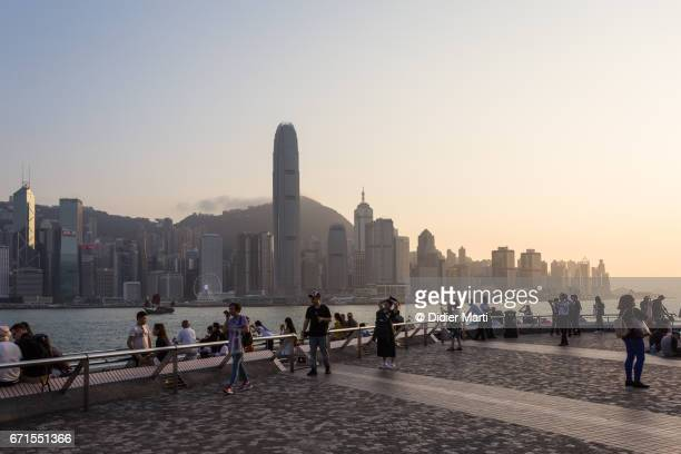 Tourists enjoy the sunset over the Victoria Harbor in Hong Kong from the Avenue of Stars
