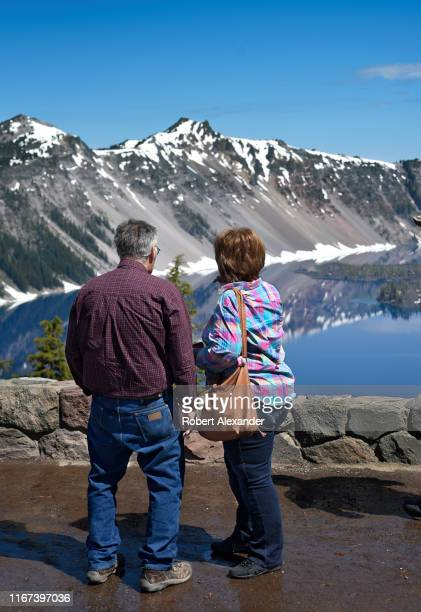 Tourists enjoy the view of Crater Lake from a scenic overlook on the rim of the lake in Oregon The lake a waterfilled caldera of an ancient volcano...