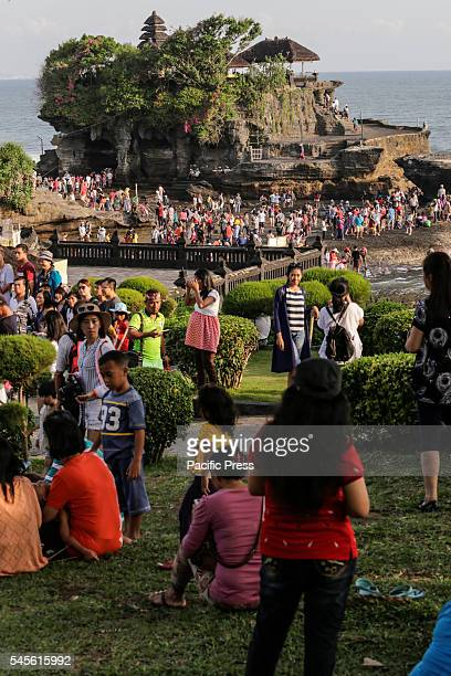 Tourists enjoy the view of Tanah Lot Temple during the third day of Eid holiday. This iconic Balinese Hindu Temple was built on the top of a coral...