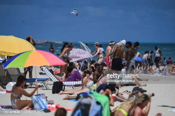 Tourists enjoy the water in Miami Beach Florida on March 18 2020 They crowded the beaches filled discos and sweated together at dances ignoring for...