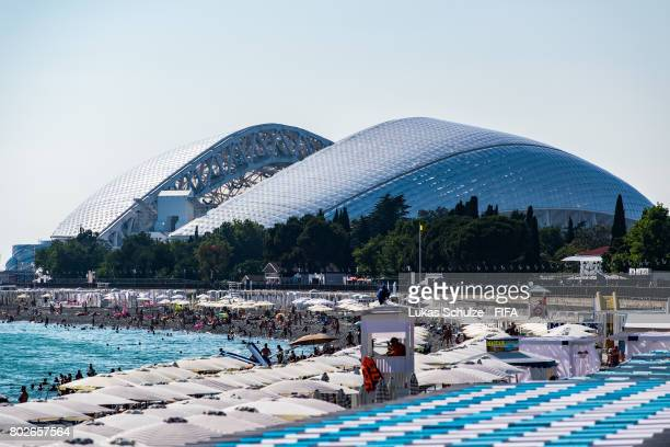 Tourists enjoy the weather on the beach of the Black Sea with a view to the Fisht Stadium on June 28 2017 in Sochi Russia