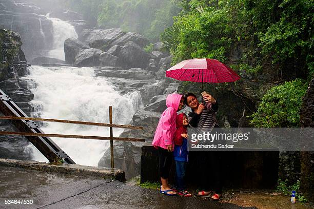 Tourists enjoy themselves taking a selfie in front of a massive waterfall during the monsoons near Shillong in Meghalaya Meghalaya is a state in...