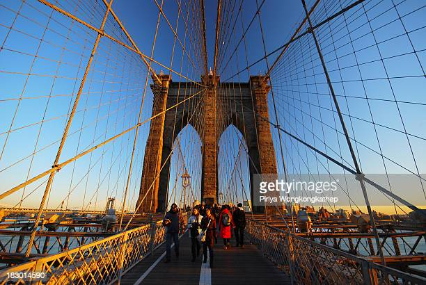 CONTENT] Tourists enjoy walking on Brooklyn Bridge and watching sunset in winter