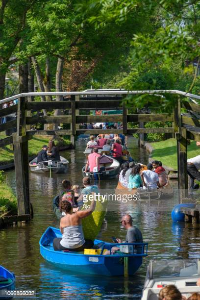 Tourists enjoying a boat tour on the canals of Giethoorn in The Netherlands