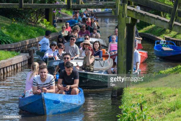 tourists enjoying a boat tour on the canals of giethoorn in the netherlands - giethoorn stock pictures, royalty-free photos & images