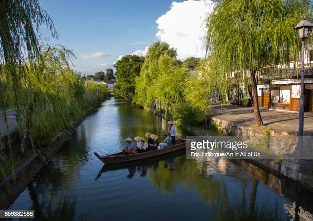 Tourists enjoying a cruise on a small boat on the river in Bikan historical quarter'n'n'n Okayama Prefecture Kurashiki Japan on August 25 2017 in...