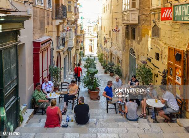tourists enjoying refreshments in cafe on narrow street in malta - valletta stock pictures, royalty-free photos & images