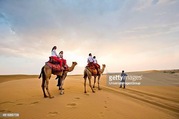 Tourists enjoying the camel safari in a desert Thar Desert Jaisalmer Rajasthan India