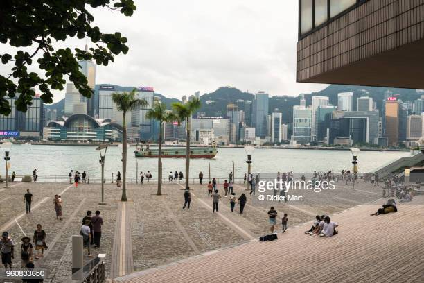 Tourists enjoying the view of the Hong Kong skyline from the waterfront promenade
