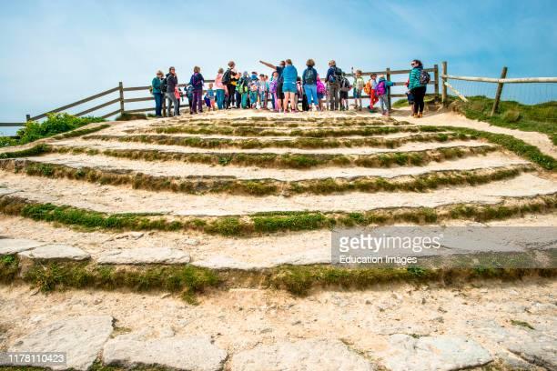 Tourists enjoying the views at Lulworth Cove on the Jurassic coast in Dorset, England, UK.