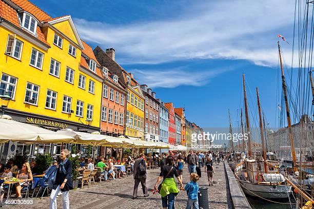 Los turistas disfrutando del cálido sol de verano en Nyhavn Promenade
