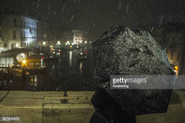 A tourists enjoys the snow on Rialto bridge on January 13 2017 in Venice Italy A heavy snowfall hit Venice after the high tide of this morning while...