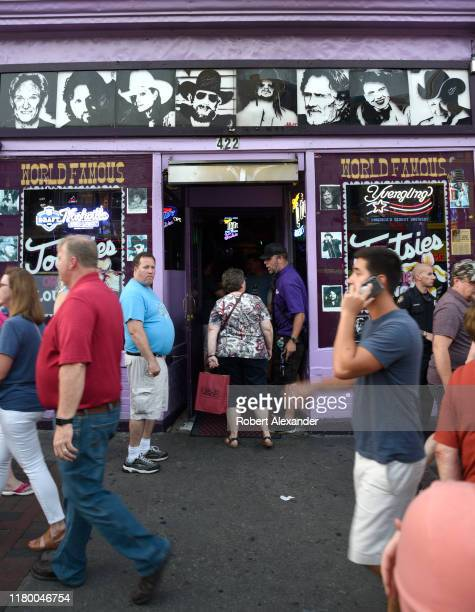 Tourists enter and walk past Tootsie's Orchid Lounge an iconic bar and live country music venue in the Lower Broadway entertainment district in...