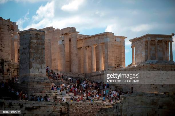 Tourists enter the ancient Parthenon temple atop Acropolis hill in Athens on July 20, 2018.