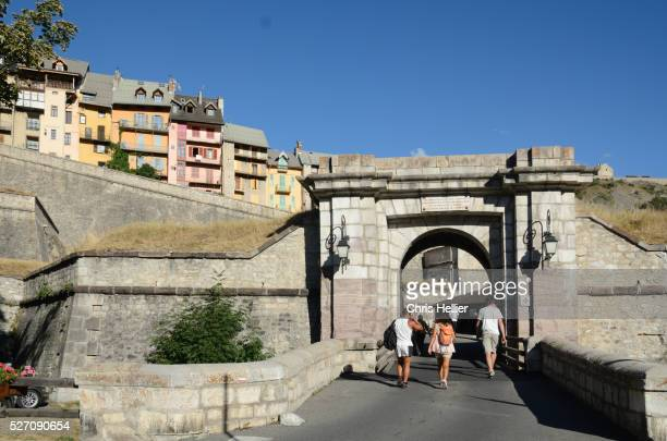 tourists entering porte d'embrun brian��on - embrun stock pictures, royalty-free photos & images