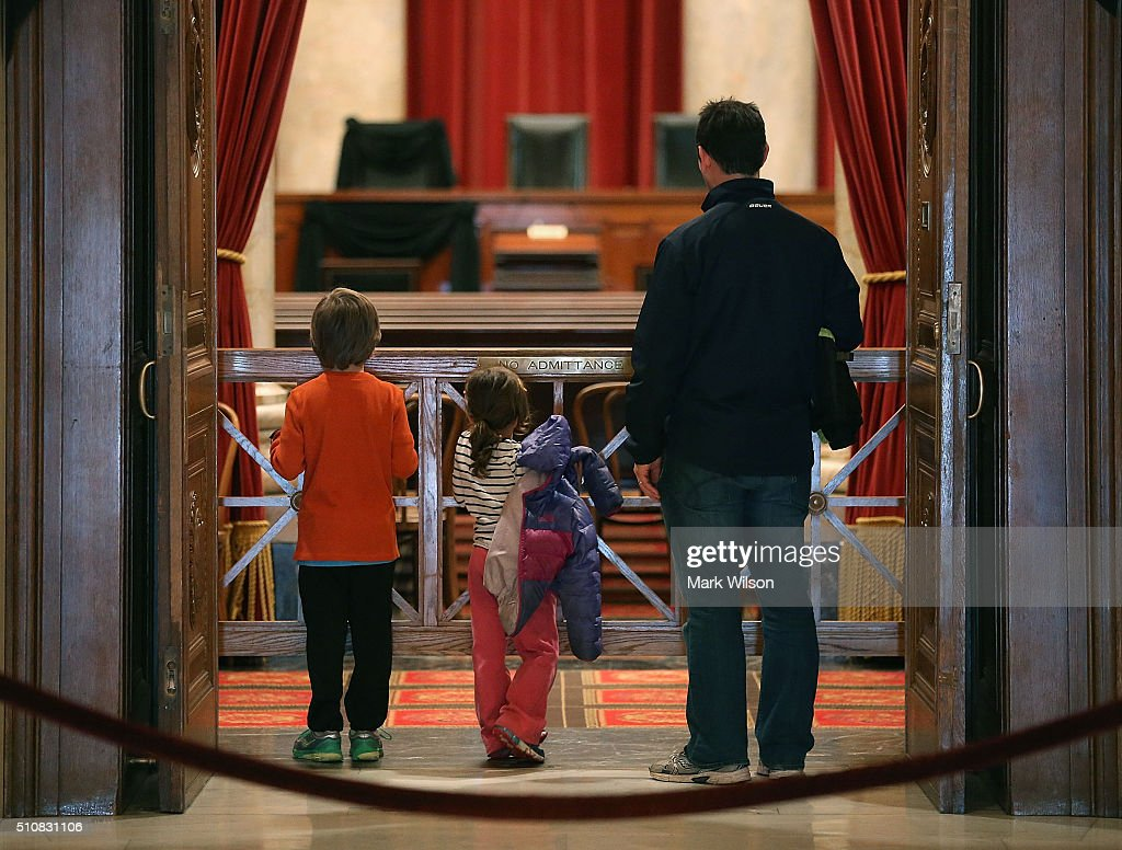 Tourists Eric Annes (R), stands with his daughter Nala (C), and son Kaelen, as they look into the chamber of the US Supreme Court where a black wool crepe cloth covers the bench and seat where the late Justice Antonin Scalia would sit when court was in session, February 17, 2016 in Washington, DC. Justice Scalia died on February 13 during a hunting trip in Marfa, Texas.