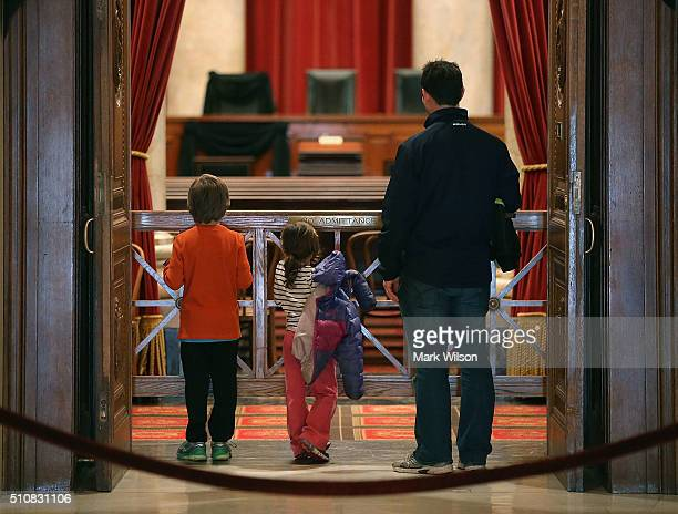 Tourists Eric Annes stands with his daughter Nala and son Kaelen as they look into the chamber of the US Supreme Court where a black wool crepe cloth...