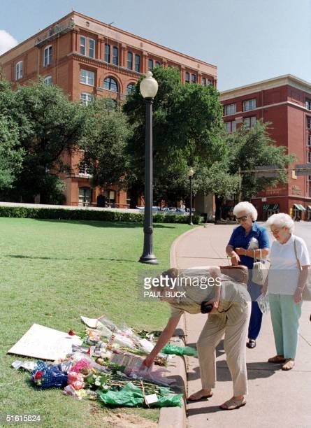 Tourists examine flowers and notes left at a makeshift memorial to John F Kennedy Jr 20 July 1999 at Dealy Plaza in Dallas Texas the place where his...