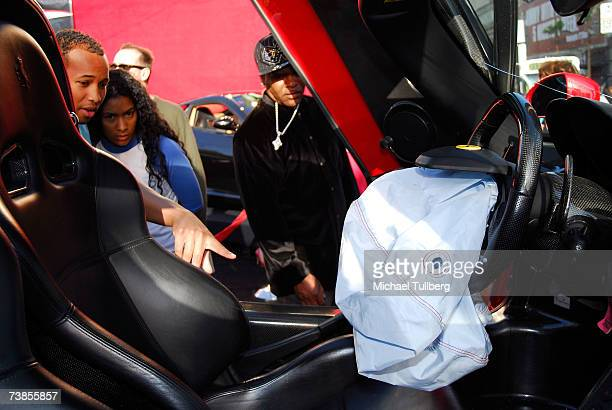 Tourists examine the airbag inside the wrecked remains of an Enzo Ferrari that saved the life of actor Eddie Griffin at a memorial service held for...