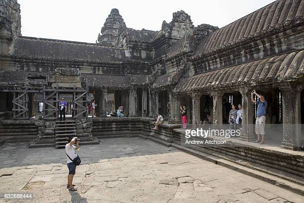 Tourists explore and photograph within one of the galleries in the ancient temple complex of Angkor Wat Siem Reap Cambodia Angkor Wat is one of...