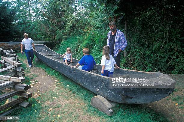 Tourists explore replica of dugout canoe at the Lewis and Clark expedition headquarters of the Fort Clatsoo National Memorial
