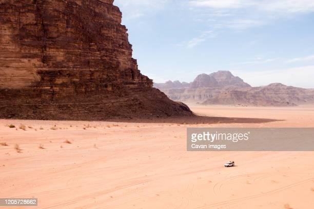 tourists explore the vastness of the wadi rum desert in jordan. - internationaal monument stockfoto's en -beelden