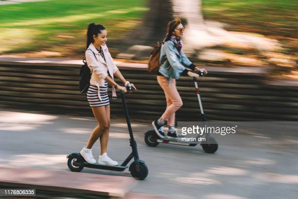 tourists exploring the city on motor scooters - electric scooter stock pictures, royalty-free photos & images