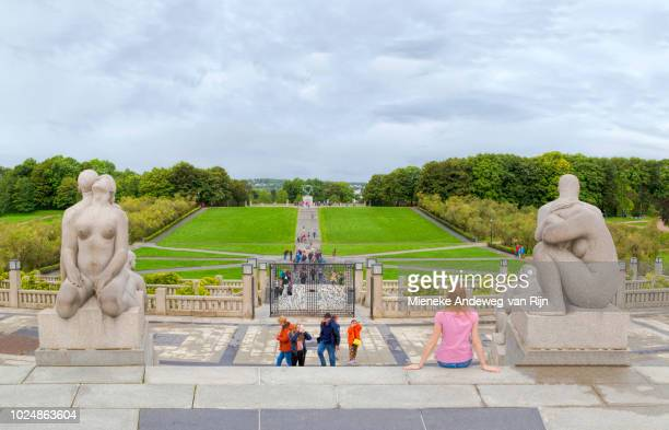 Tourists exploring Vigeland's sculpture park with more than 200 sculptures in bronze, granite and wrought iron, in Frognerpark, Oslo, Norway.