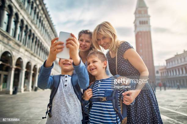 Tourists family talking selfie in Piazza San Marco in Venice