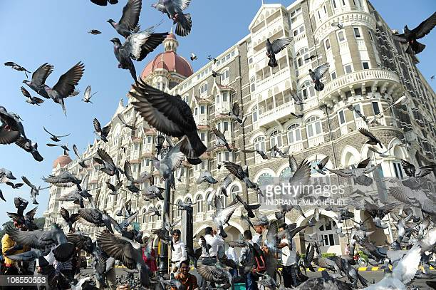 Tourists feed pigeons on November 5 2010 at the landmark Gateway of India across the Taj Mahal Palace Hotel in Mumbai where US President Barack Obama...