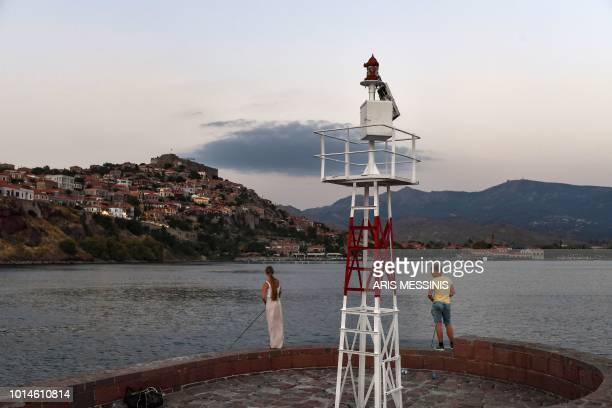 Tourists fish at the port of Mithymna on the northeastern island of Lesbos on August 3 2018
