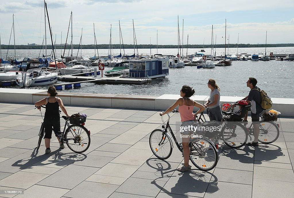 Tourists from Britain walk their bikes along the boardwalk at the marina of artifiticial Senftenberger See lake on August 26, 2013 in Senftenberg, Germany. Senftenberger See was once an open-pit lignite coal mine flooded after it shut down in the late 1960s, and today it is popular among tourists, windsurfers and fishermen. In a development project initiated by state government, other nearby former open-pit mines that once evoked a lunar landscape are being turned into lakes in a long-term rejuvenation effort that is also intended to make the area a viable tourist destination. Mineral residue from the mines, however, is proving a difficult stumbling block that is making many of the new lakes too acidic to sustain marine life in the short term.
