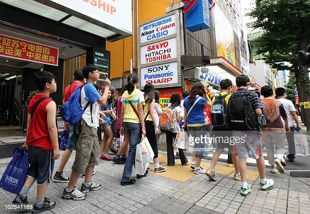 Tourists from China leave a Laox Co shop in the Akihabara district of Tokyo Japan on Wednesday June 30 2010 Chinese shoppers in Akihabara outspend...
