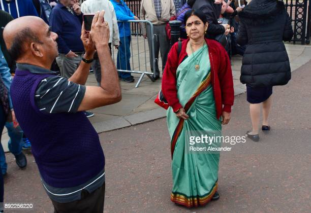 Tourists from India take souvenir photographs in front of Buckingham Palace in London England