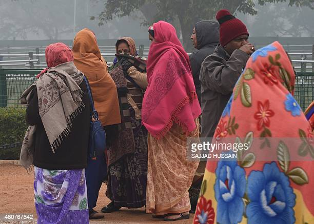 Tourists from India's western Gujarat state clad in thick shawls to ward off the cold visit the landmark India Gate monument on a foggy morning in...