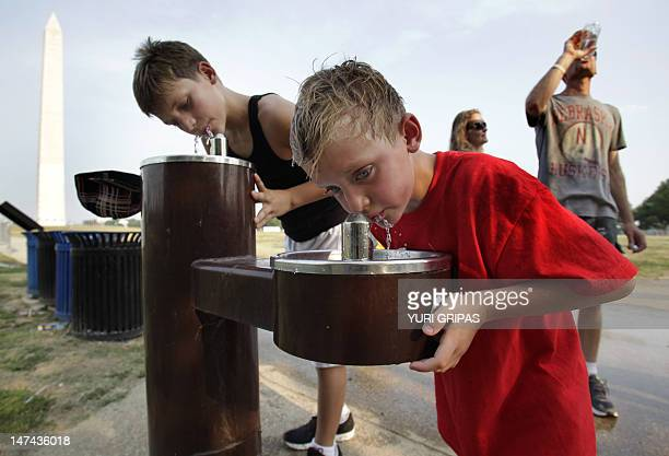 Tourists from Nebraska Brient and Beau Wood drink water June 29 2012 in Washington DC where temperatures have reached 104 degrees Fahrenheit breaking...