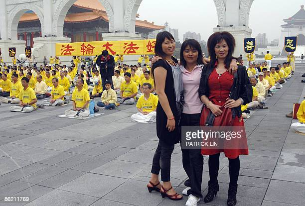 Tourists from the Chinese province of Guizhou have their photo taken in front of practitioners of the Falungong spiritual movement in Taipei on April...
