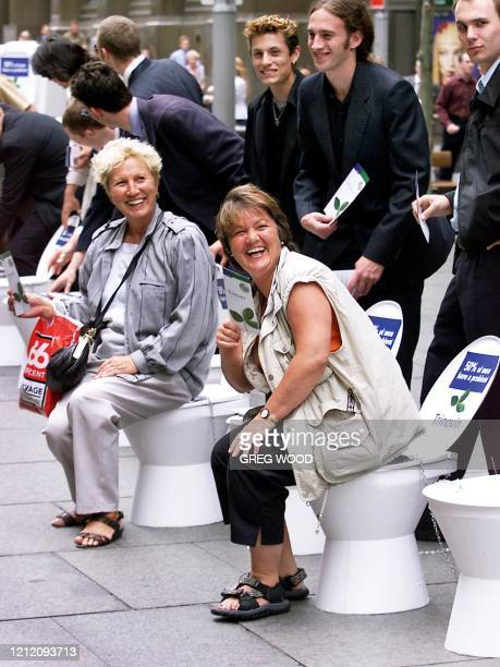 Tourists Gabi Reiter from Croatia and Roswitha Koenig of Germany laugh as a friend photographs them sitting on toilets being used to help promote...