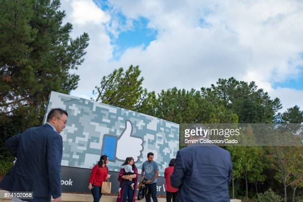 Tourists gather and take photographs outside the sign for Facebook at the headquarters of social network company Facebook in Silicon Valley Menlo...