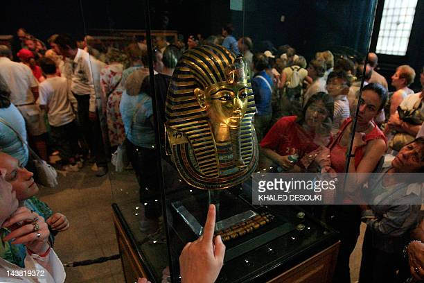 Tourists gather around the mask of the most famous Pharaonic royal King Tutankhamun at the Egyptian Museum in Cairo on April 13 2008 The young king...