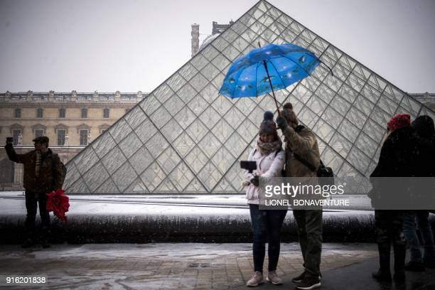 Tourists gather as snow falls in front of The Louvre Pyramid in Paris on February 9 2018 The northwest of France has received fresh snowfall...