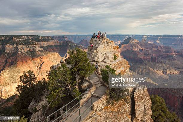 Tourists gather at a viewpoint overlooking a grand canyon landscape.